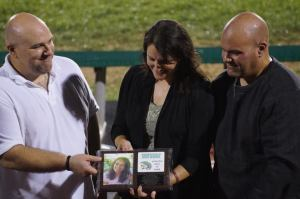 Kass's brothers and sister: (l to r) Tom, Krista, and Tim accept the plaque during the half-time ceremony.